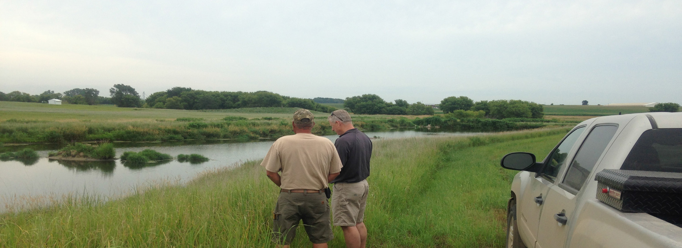 Schilling (right) with Randy Iedema, superintendent of Rural Water System No. 1, stand near a nitrate-removal detention basin.