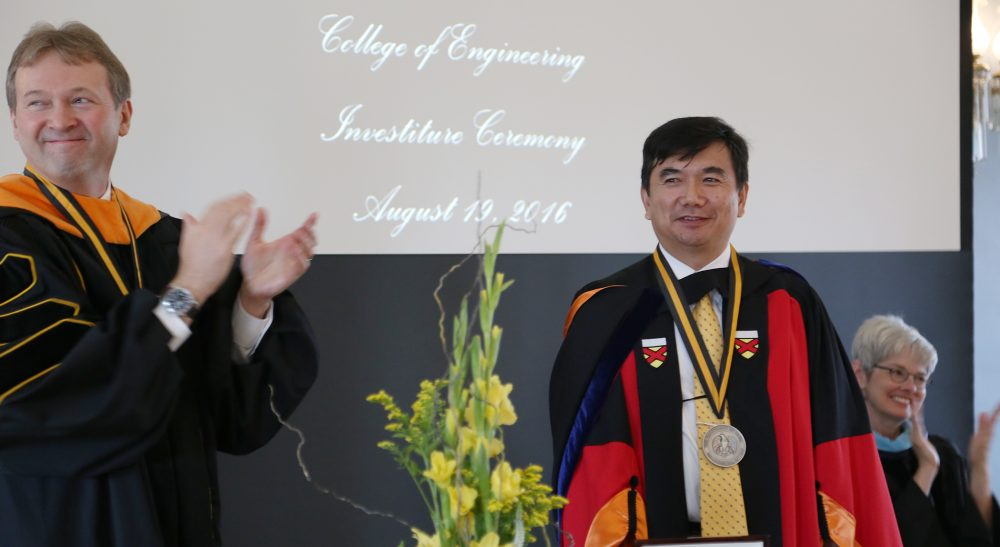 Ching-Long Lin (center) wears the medallion signifying his new status as the Edward M. Mielnik and Samuel R. Harding Professor in Mechanical and Industrial Engineering, while Dean of Engineering Alec Scranton (left) and UI Foundation President Lynette Marshall applaud to show their approval.