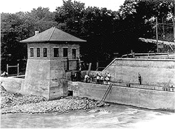 Vintage photo from the 1920s showing a small building on the riverbank and a group of students and researchers standing near an outdoor flume for river water.