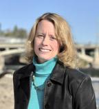 Headshot of Carmen Langel taken on the banks of the Iowa River with the Burlington Street Bridge in the background.