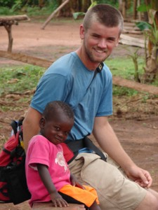 This adorable photo shows a smiling young American man seated next to a very small Ghanaian boy, who smiles shyly at the camera.