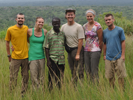 This photo shows a group of American students and a faculty member posing with a Ghanaian man in a field of tall grass.