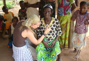 A kneeling young American woman with a stethoscope conducts a medical examination on a seated Ghanaian woman.