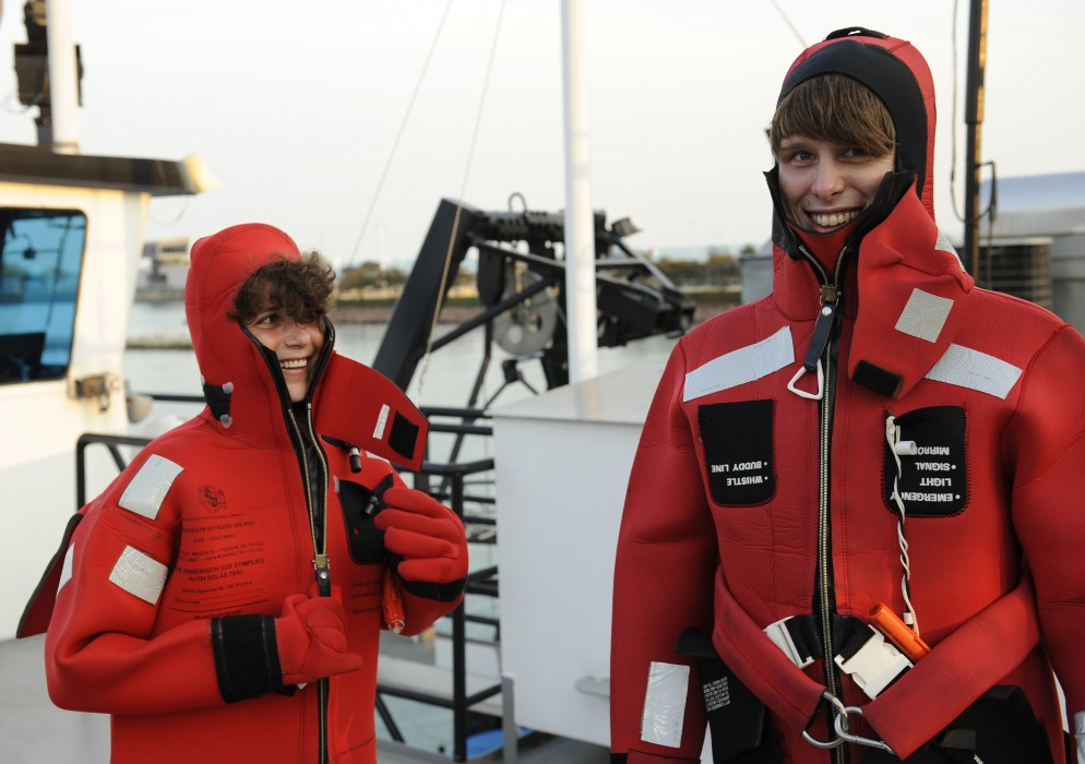 Two students wearing red wetsuits on the deck of a research vessel prepare to jump in Lake Michigan.
