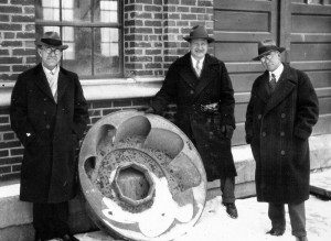 This is a vintage black and white photo that shows three men in hats and overcoats posing with a water turbine in front of the Hydraulics Lab.