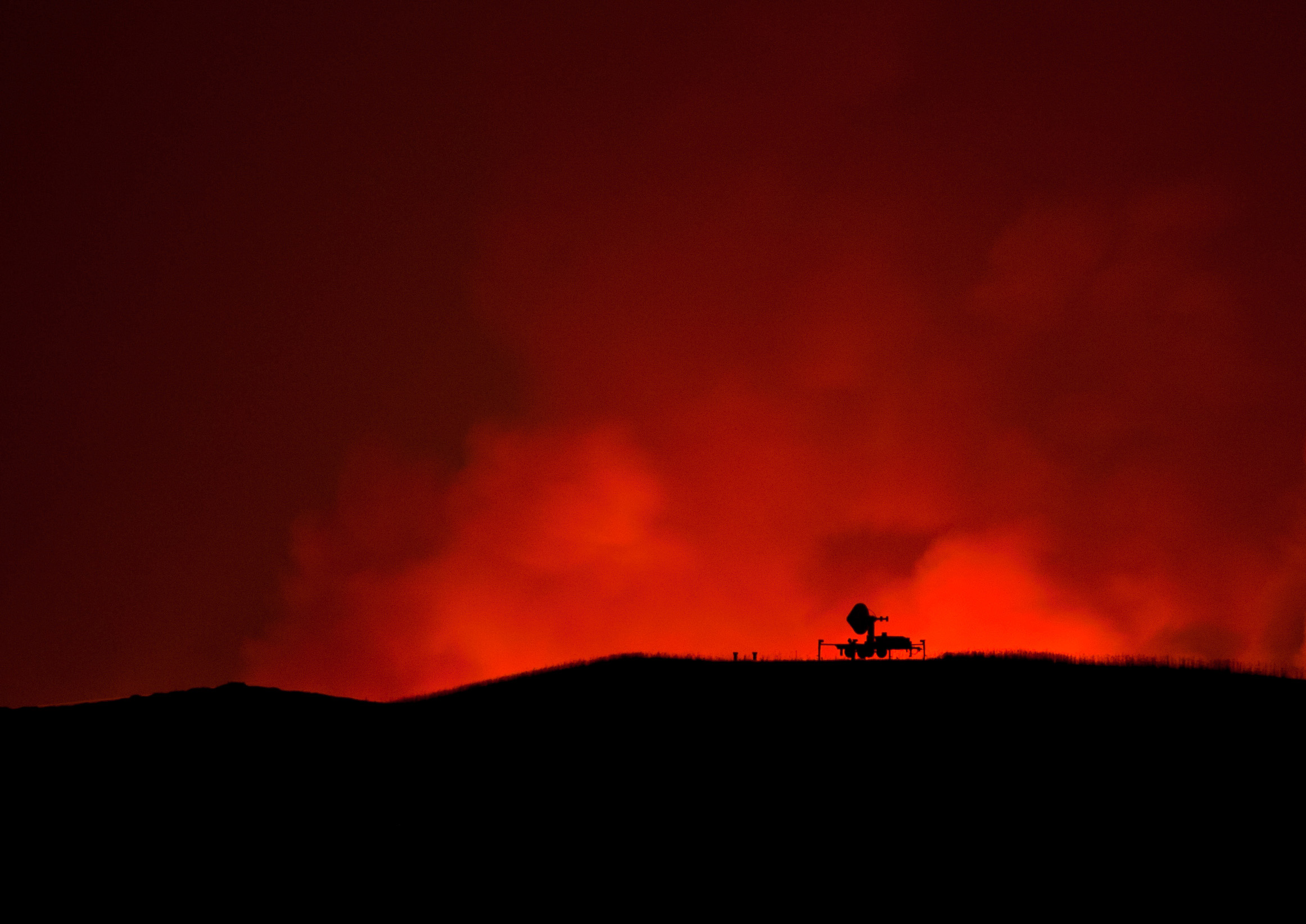 The IFC radar is silhouetted against the Iowa City Landfill fire. Photo by Aneta Goska