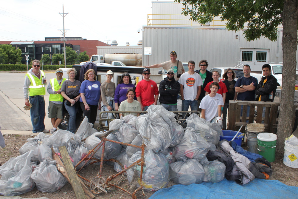 Volunteers pose with the impressive pile of trash they picked up along the Iowa River on Saturday, June 2.