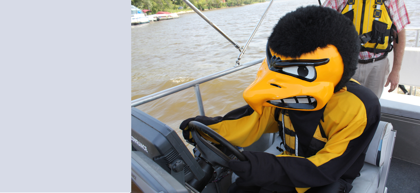 University of Iowa mascot Herky drives one of the boats used for river research at LACMRERS.