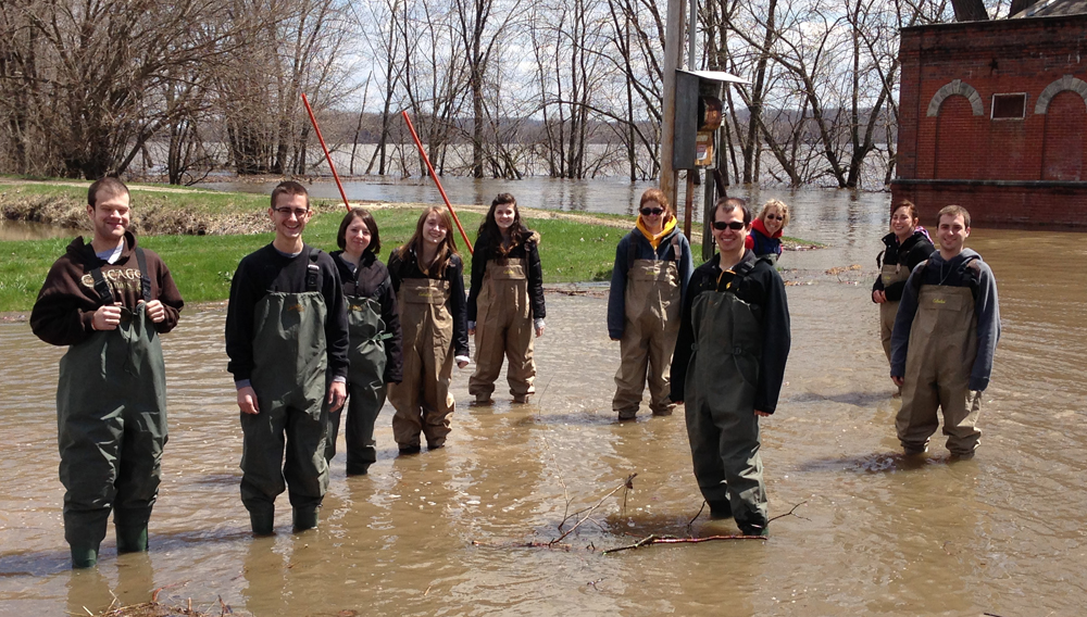 Students from Barbara Eckstein's class stand in the flood water.