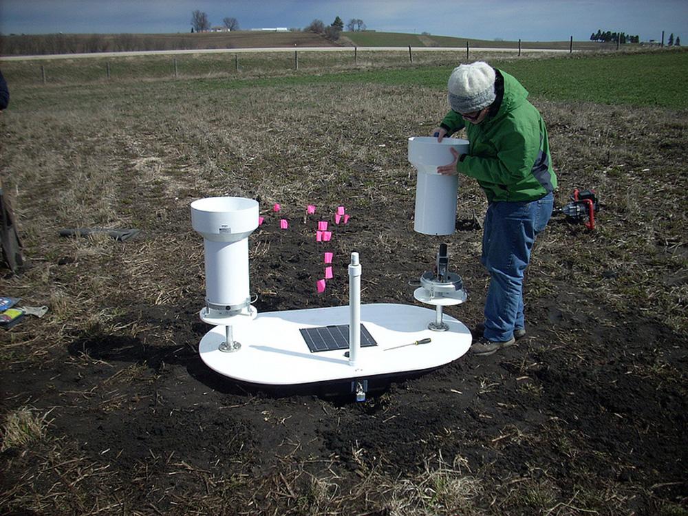 An IFC researcher installing a rain gauge.