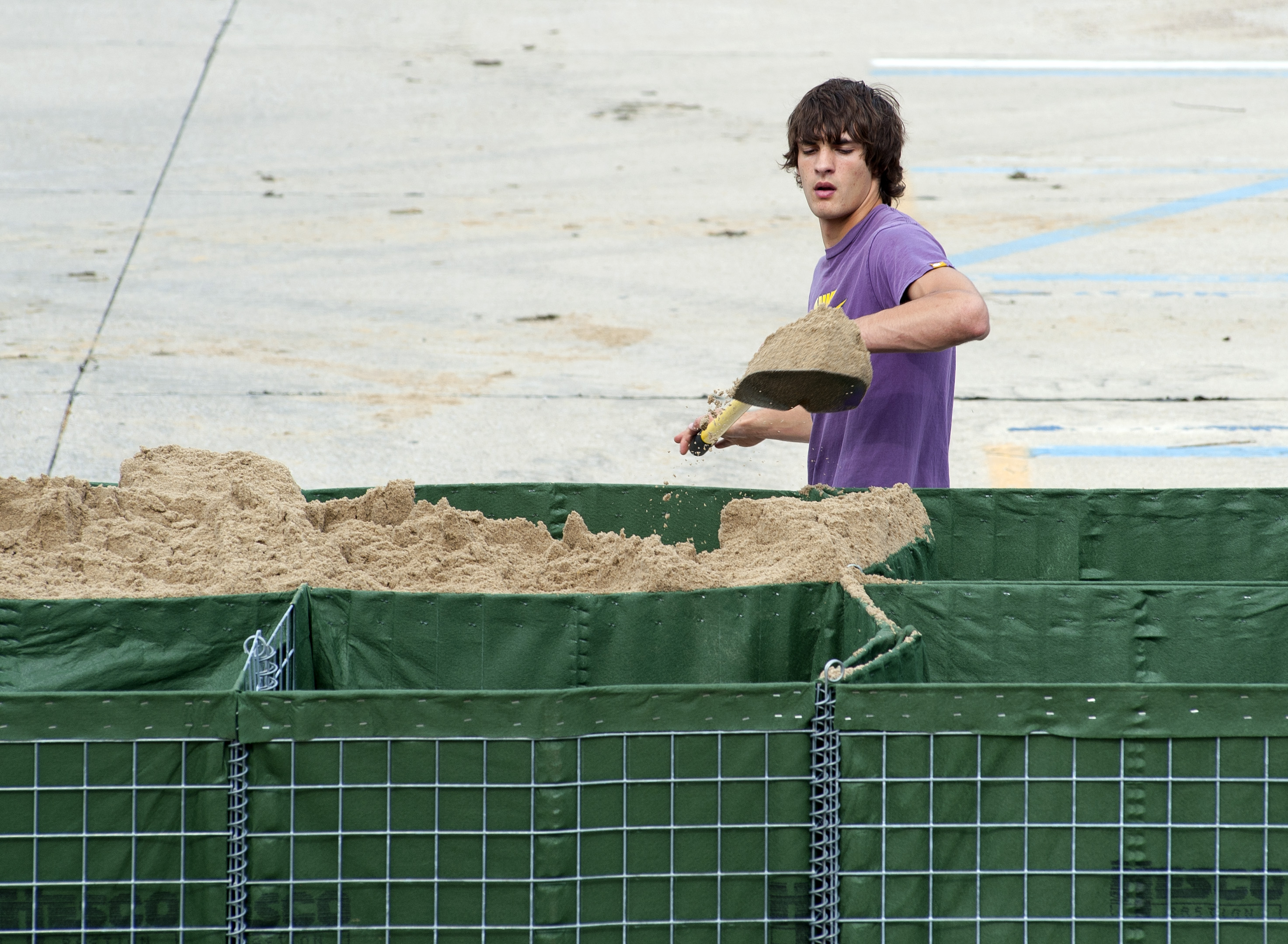 A student volunteer helps fill a HESCO barrier with sand.