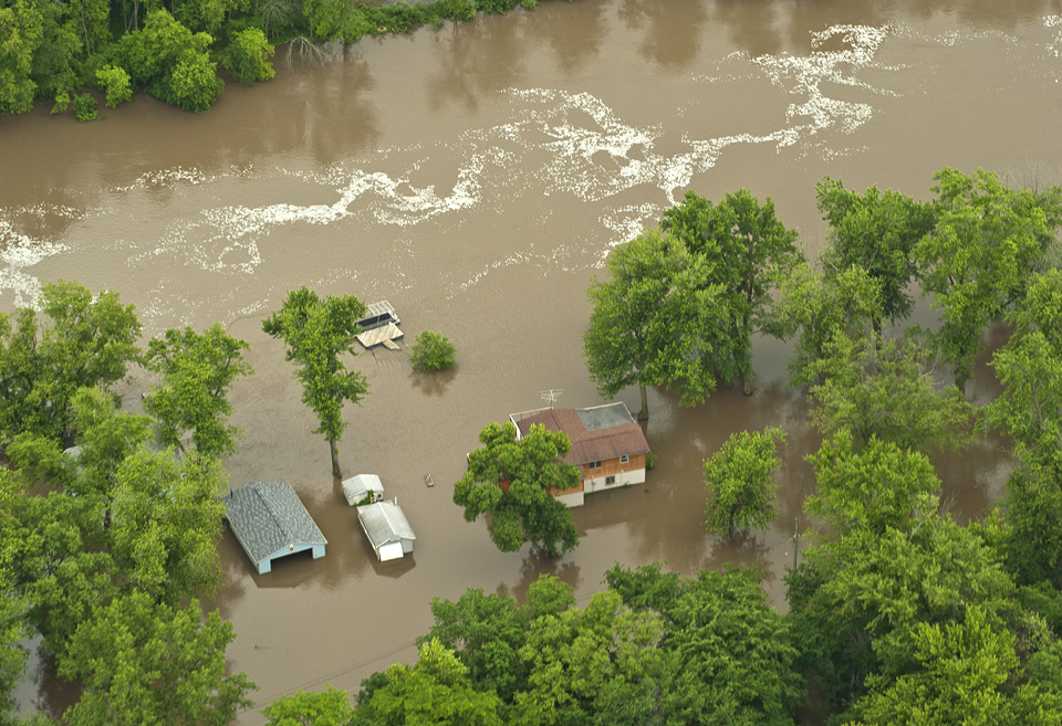 A home and outbuildings are swamped by floodwaters.