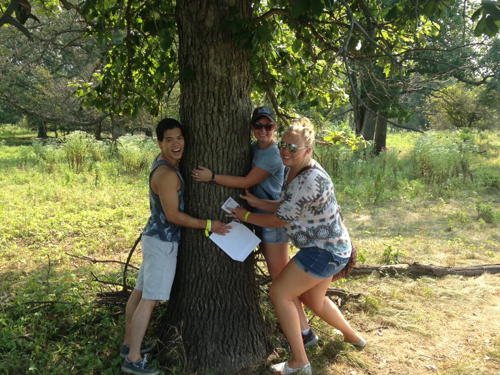 """Tree-hugging"" students investigate the 2008 flood line evident on an oak tree. (L to R): Zach Wendland, Maddison Wignall, and Alena Newgren."