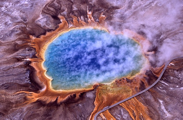 While most people are familiar with microbes that occur above ground—such as this orange-colored colony surrounding Grand Prismatic Spring at Yellowstone National Park—microbes also occur around hydrothermal vents on the ocean floor, at depths where light cannot penetrate and where they trap carbon using chemical energy instead of sunlight. Photo by Jim Peaco, National Park Service, via Wikimedia Commons.