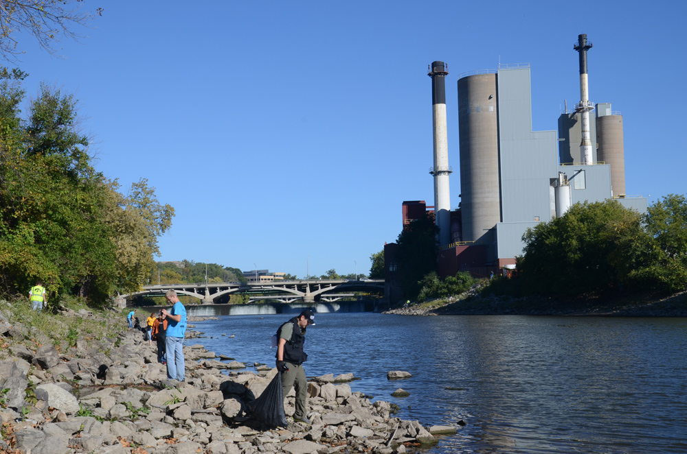 Volunteers pick up trash along the banks of the Iowa River.