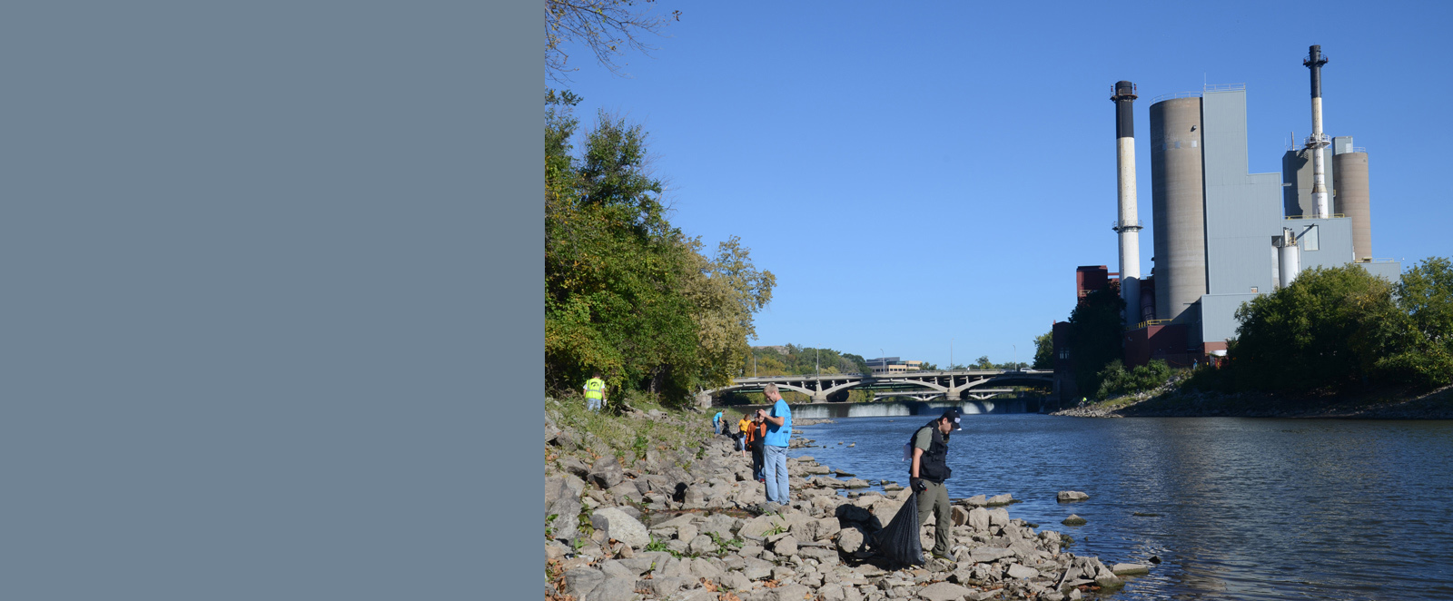 Volunteers gather trash along the banks of the Iowa River.