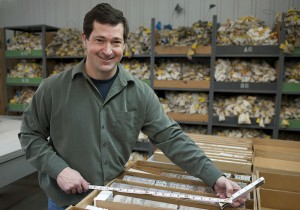 A man works in the IGS's Rock Library, holding a tape measure to measure a rock core sample.