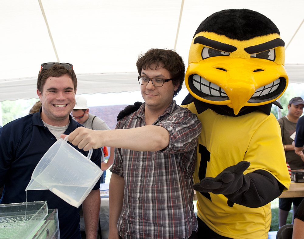 Iowa Flood Center researchers Scott Rowe (left) and Felipe Quintero show Herky how floodwaters move through the watershed.