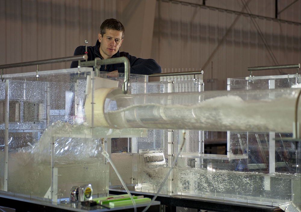 Troy Lyons watches water move through a model simulating some of the many interception chambers, drop shafts, and orifices that will capture the flow into London's tunnel system.