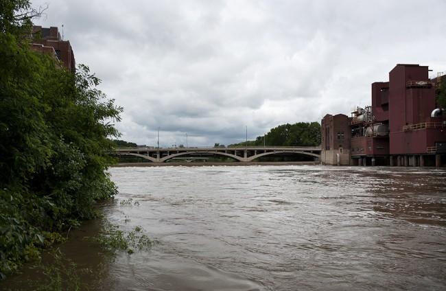 The swollen Iowa River flows past the University of Iowa Power Plant.