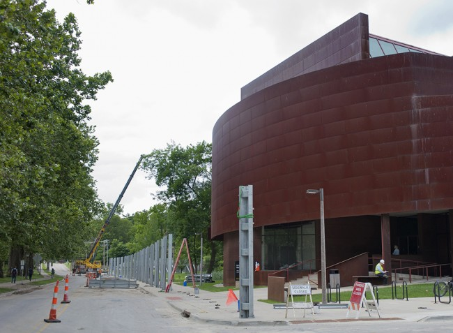 Work crews begin the task of setting up the invisible flood wall around the Art Building West.