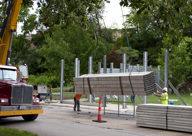 """The """"invisible flood wall"""" becomes visible as crews erect the structure around the Art Building West."""