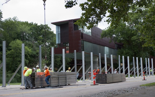 Work crews erect the invisible flood wall around the Art Building West.
