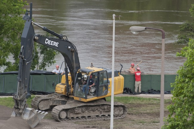 Crews erect HESCO barriers to serve as temporary flood walls along the Iowa River on the UI campus.