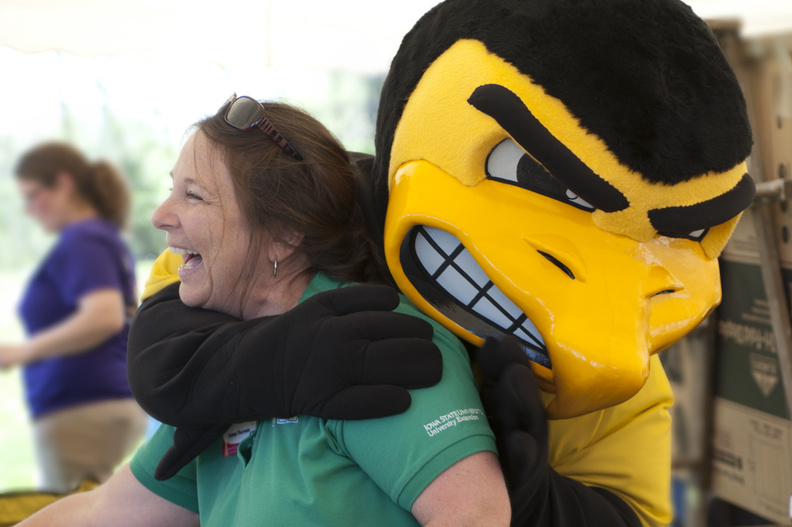 Herky hugs a new friend at the STEM festival.