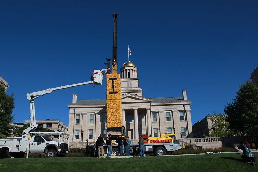 Old Capitol looks on as a crane sets the 2014 corn monument upright on the Pentacrest.