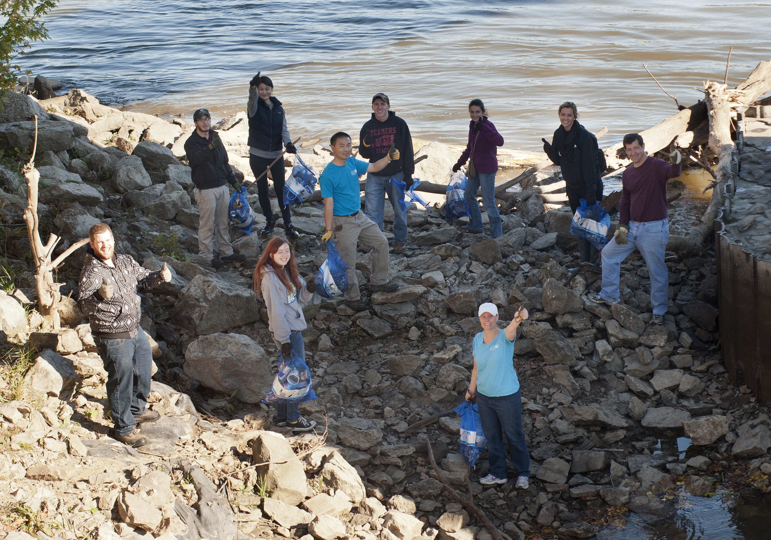 Volunteers pose by the Iowa River.