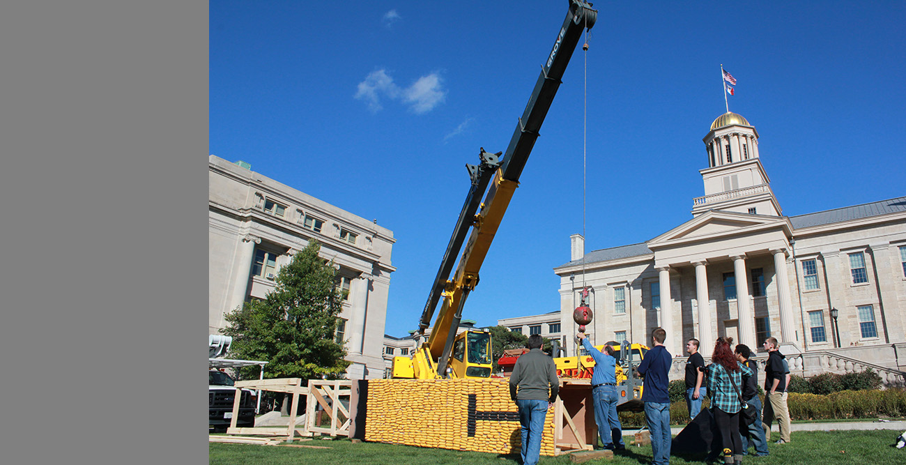 Old Capitol looks on as a team of students and faculty work to raise the 2014 corn monument — with the help of a crane.