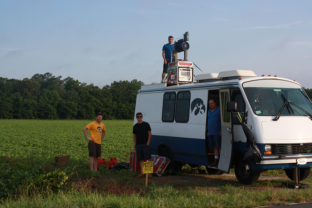 Researchers stand next to, on top of, and inside a van.