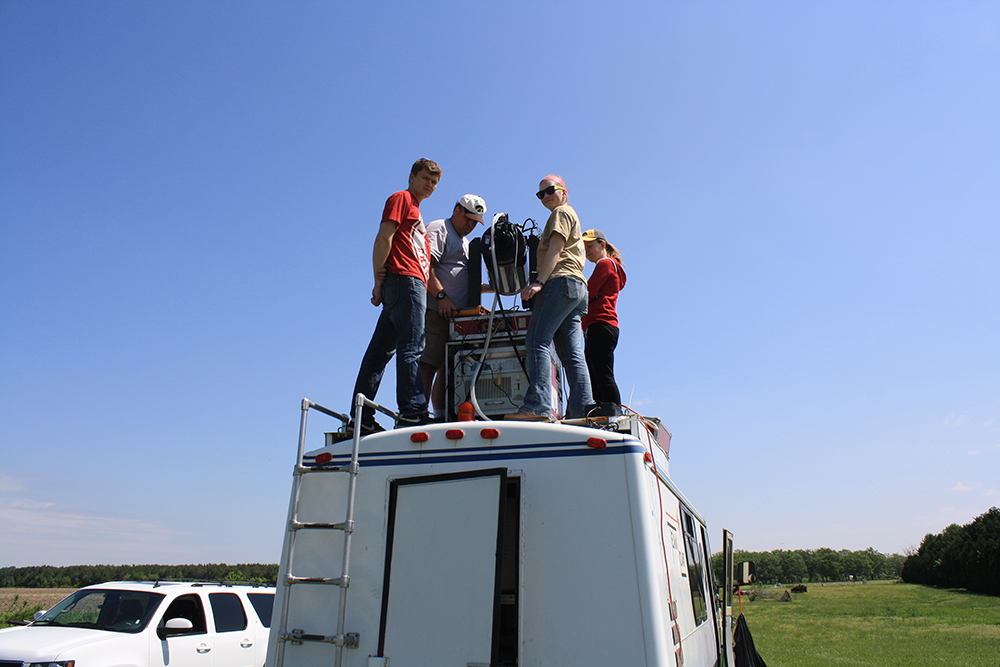 Researchers on top of a van.