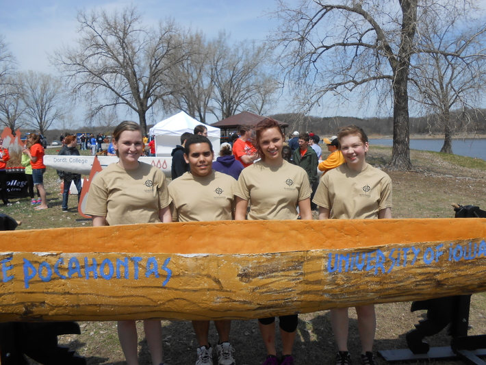 Four students stand behind a canoe.