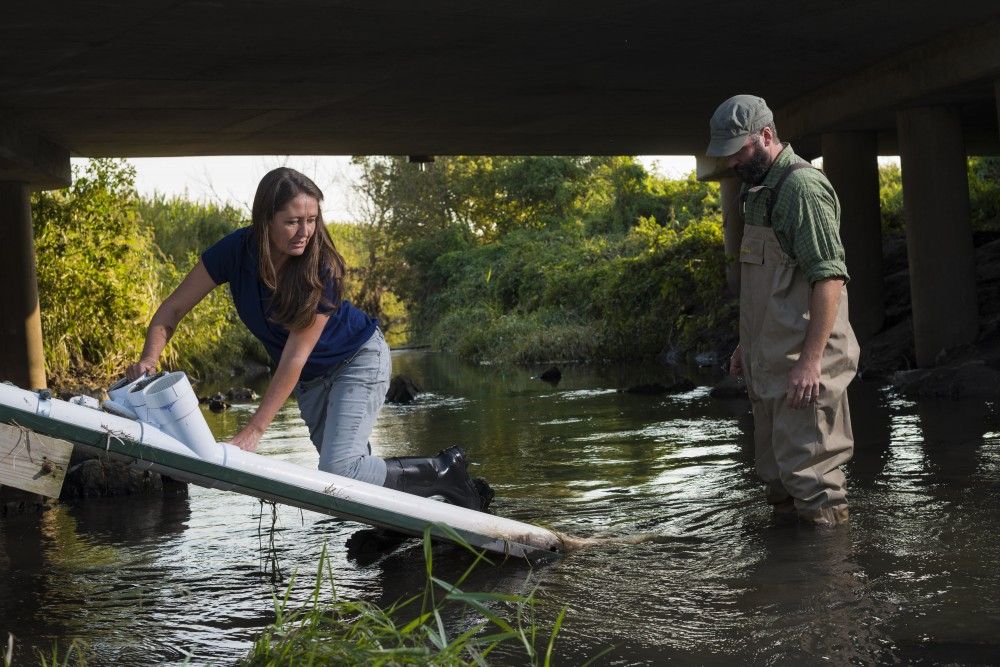 A woman in jeans and waders cleans mud out of the housing of a water-quality sensor, while a man also in waders looks on. Both stand in the shallow water of a stream.