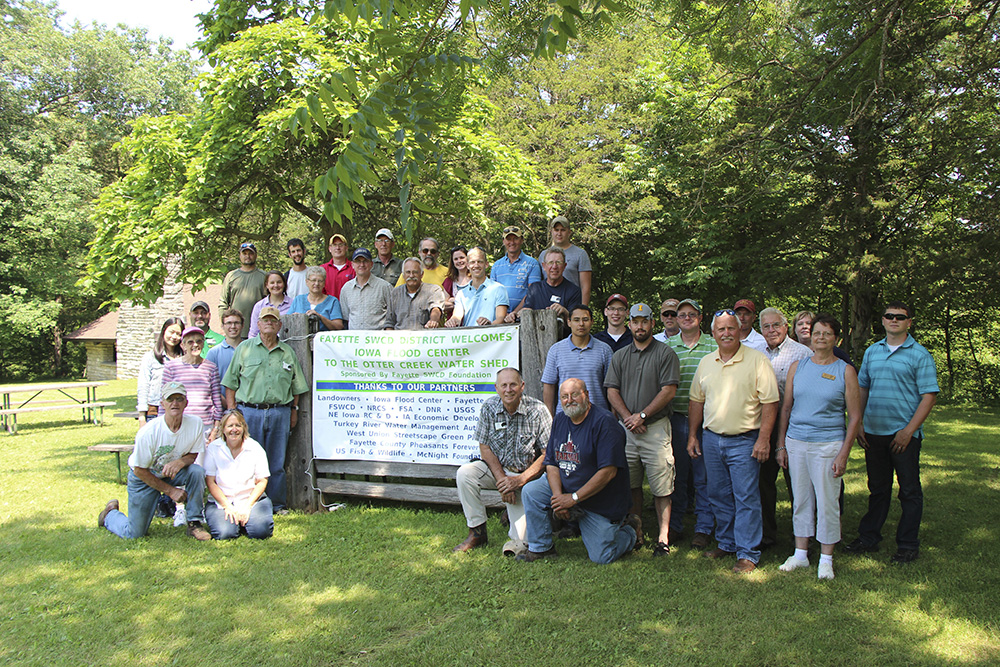A group of people, mixed in age and gender, pose with a sign for the Otter Creek Watershed. The scene is green and leafy.