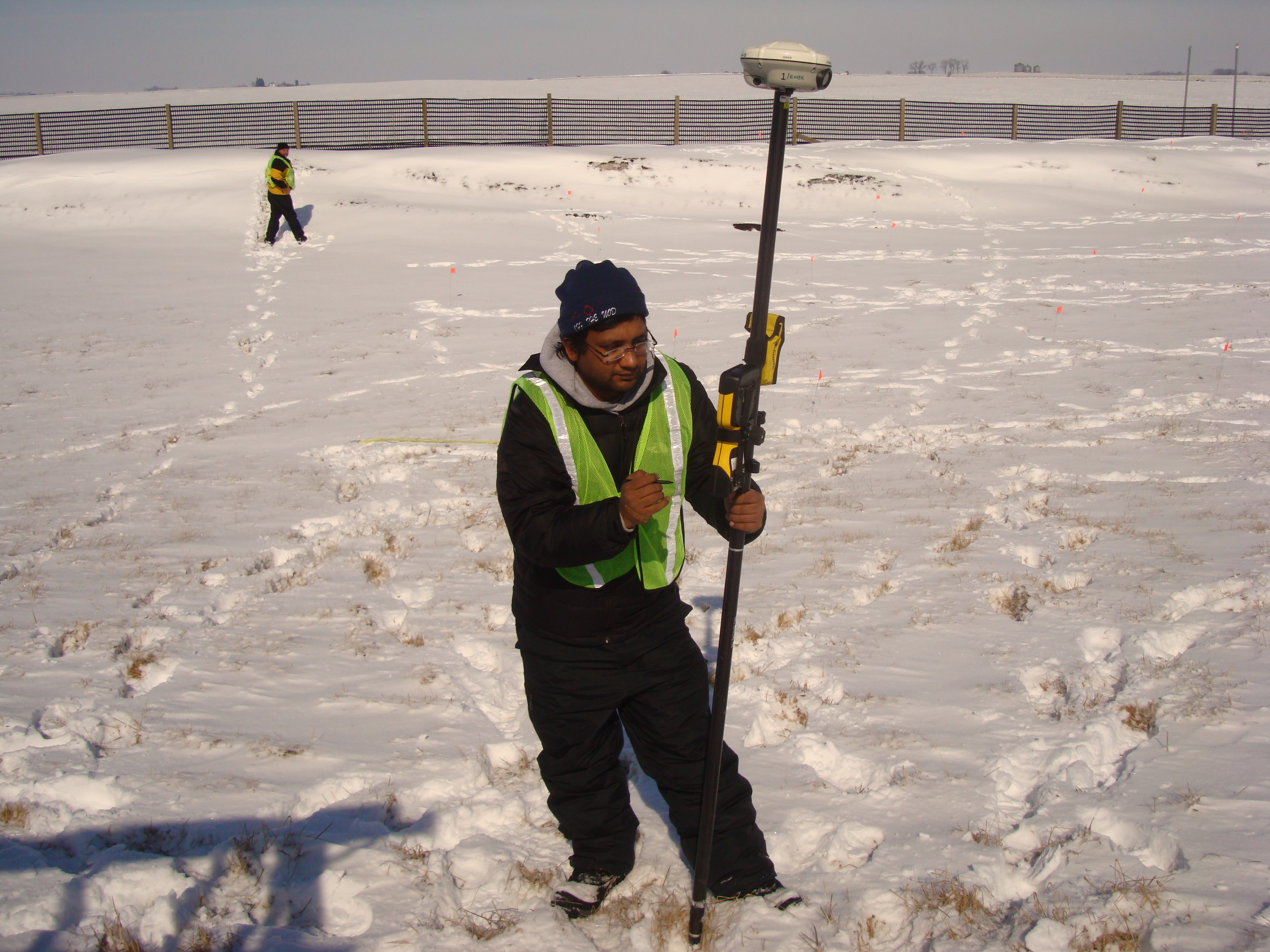 Researcher holds equipment up in a snowy field.