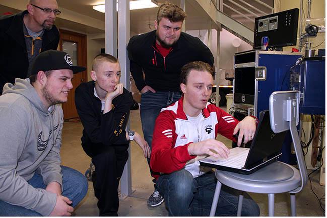 The Rocket Club crowds around a computer.