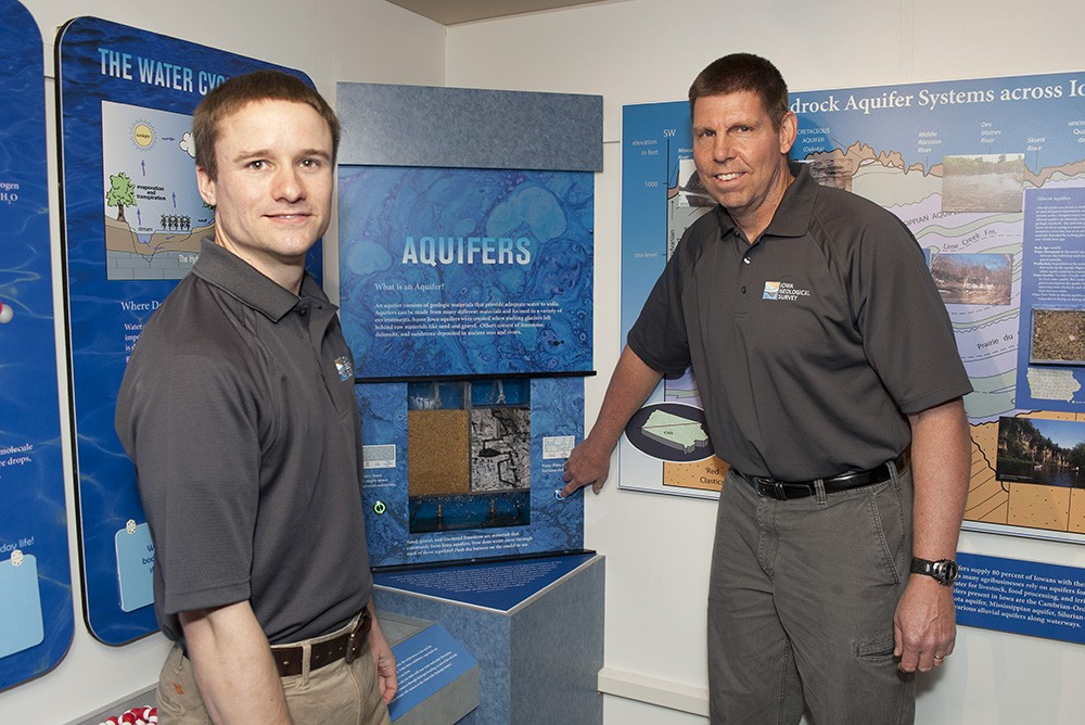 Jason Vogelgesang (left) and Mike Gannon, both of the Iowa Geological Survey, show off the new hands-on aquifer exhibit.