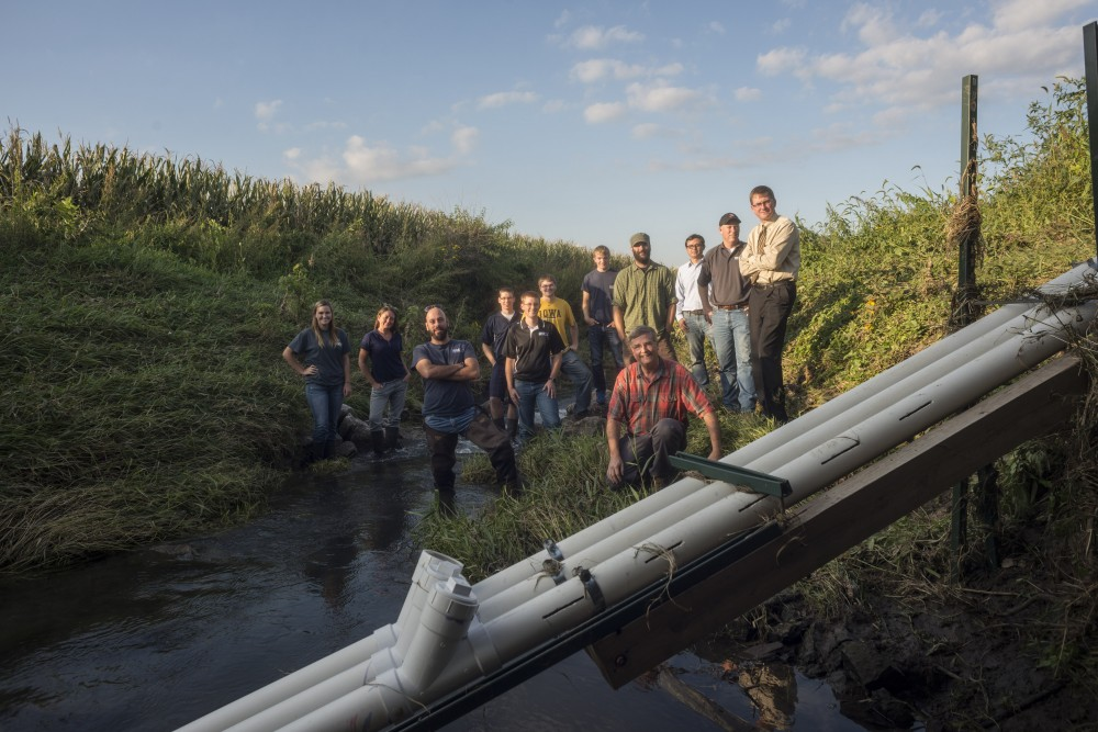 A group of students and researchers, many in waders, pose in an Iowa stream with a water-quality sensor in the foreground.