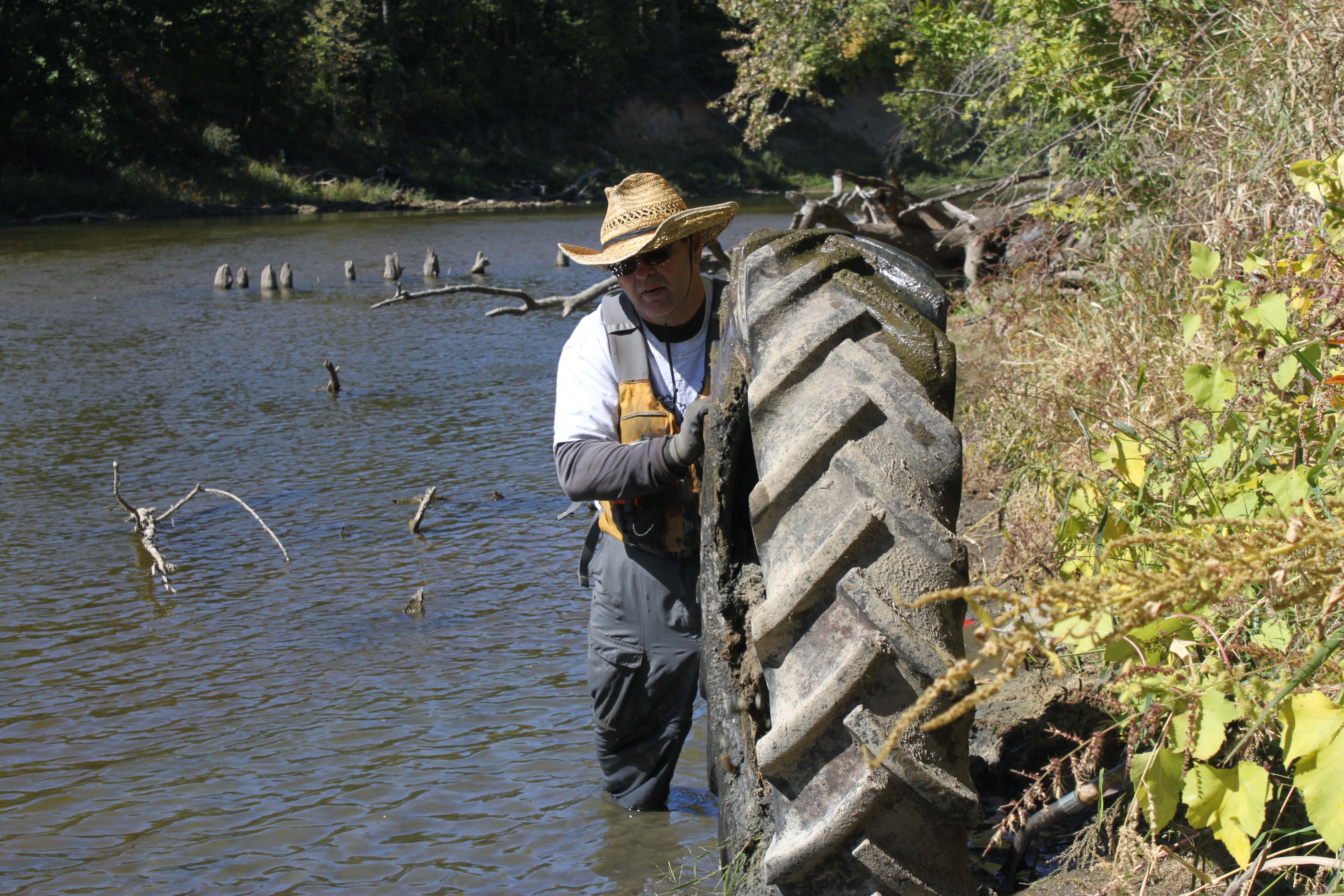 A volunteer pulls a tire out of the Iowa River.