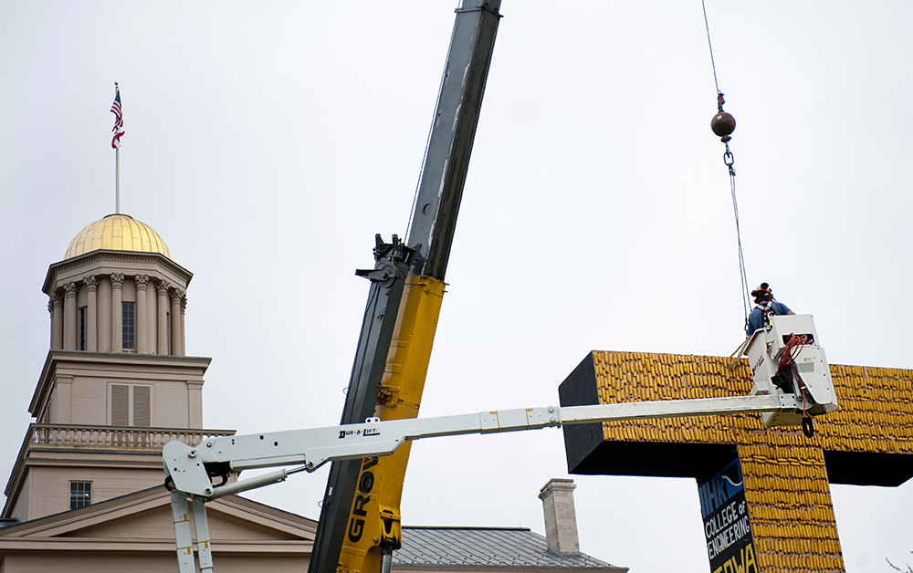 A crane sets the 2015 Corn Monument in place on the Pentacrest.