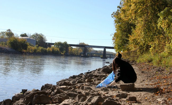 Girl picking up trash by the Iowa River.