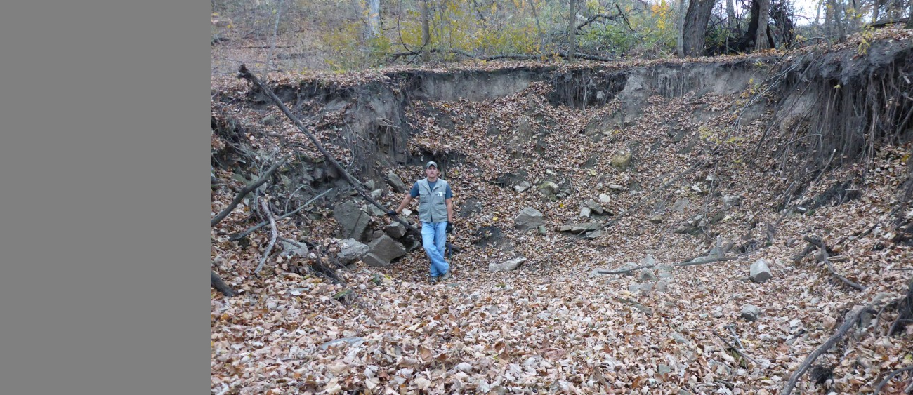A geologist stands in a sinkhole.