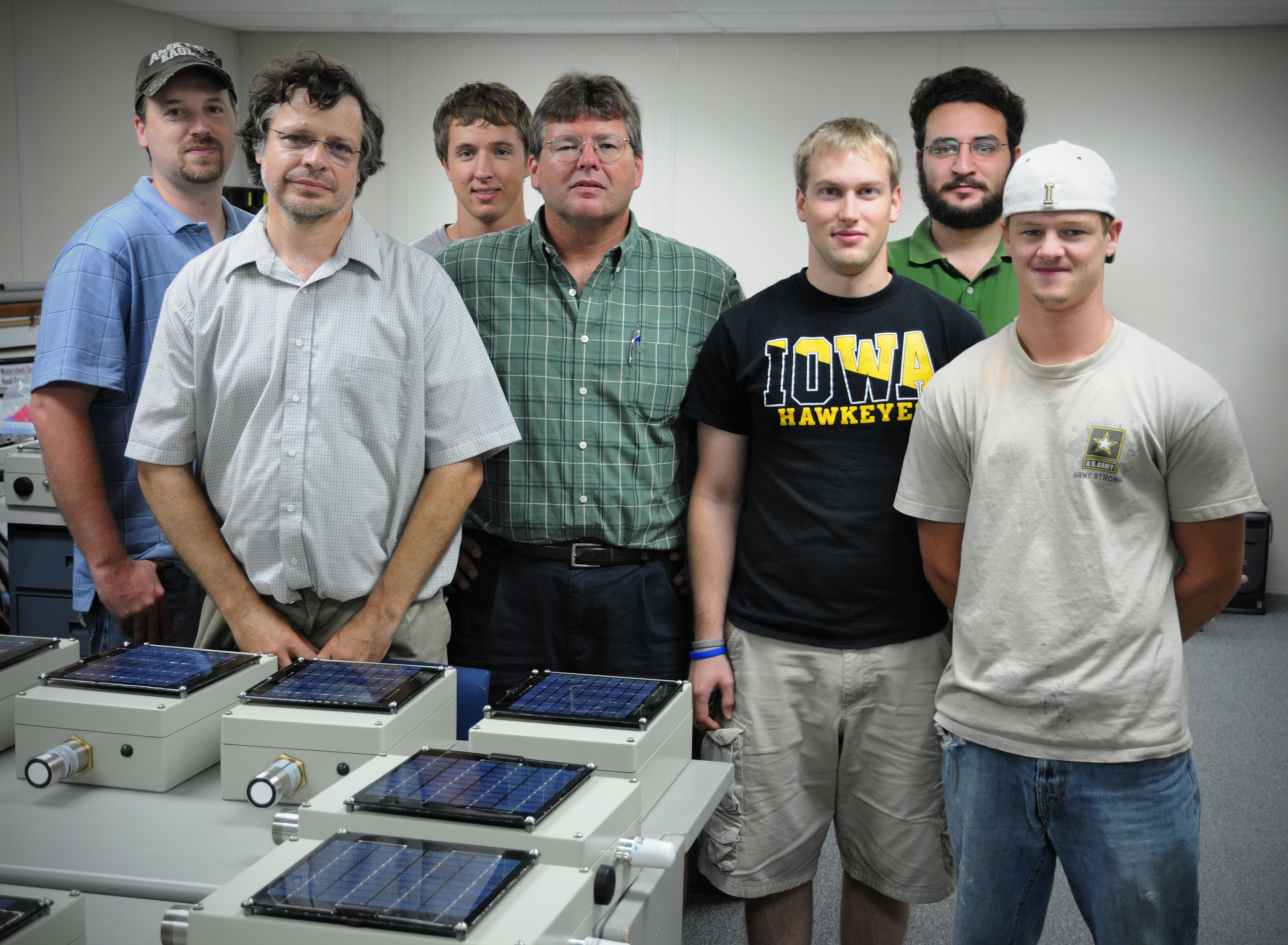 Researchers pose next to stream stage sensors.