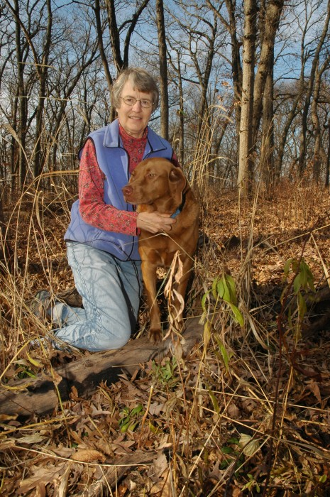 Connie Mutel with her Irish setter outdoors in the woods.
