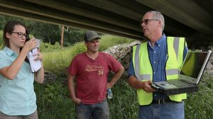 IIHR's Chris Jones (right) shows onlookers the IWQIS site, where the new sensor was already reporting data.