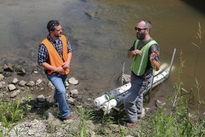 IIHR's Tom Stoeffler (right) talks with Dan Mahoney, watershed coordinator of the West Fork Crooked Creek Demonstration Project. The new water-quality sensor can be seen behind them.