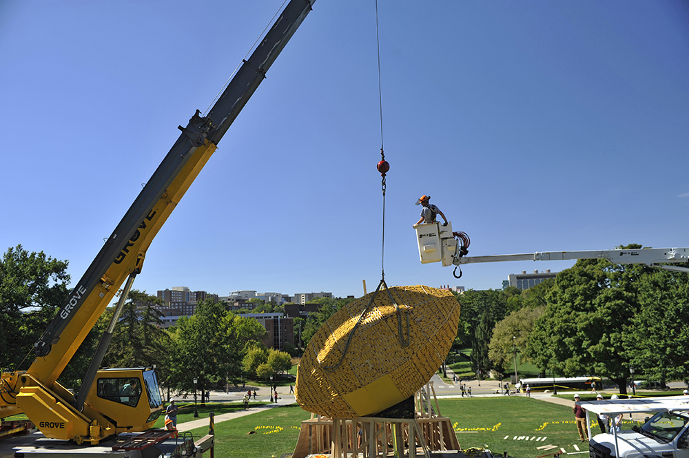 A crane lowers the corn monument onto its perch near Old Capitol on the Pentacrest. The University of Iowa's student ASCE chapter designed and built the corn monument, with the help of faculty advisers Bill Eichinger and Allen Bradley.